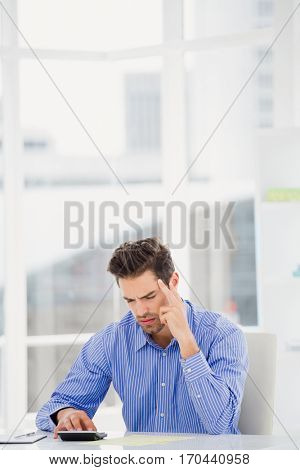 Businessman calculating accounts on a calculator in office
