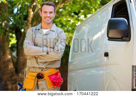 Handyman with tool belt around waist standing next to van