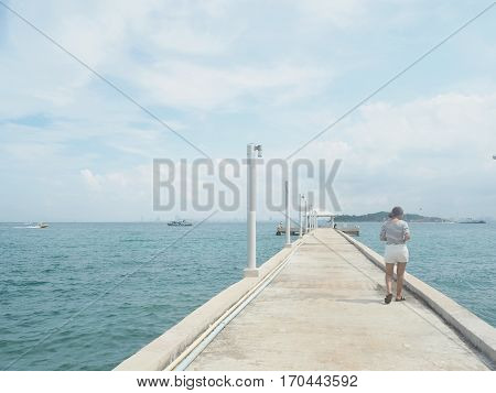 concrete pier on sea/ocean with blue sky background in Thailand.
