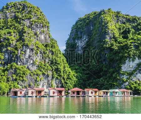 Floating fishing village with rock island in background, Ha Long bay, Vietnam