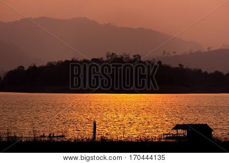Sihouette houseboat and long-tailed boat in the river with mountain view on the sunset Sangkhlaburi Kanchanaburi Thailand