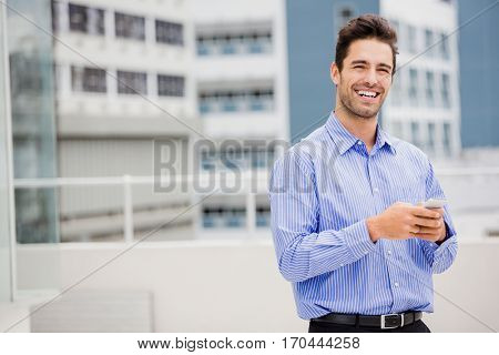 Portrait of businessman text messaging on mobile phone on office terrace