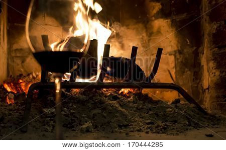 Romantic Glass of Red Wine in Front of rustic fireplace with hot red coals conceptual relaxation tranquil image for valentines day card or social network greeting with room for copy or hashtag