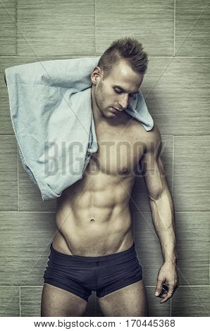 Handsome semi-naked muscular young man in bathroom with towel, looking at camera