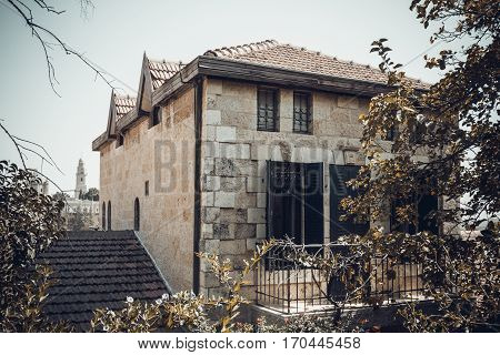 The stone house built of white stone tiled roof and windows with shutters the historic neighborhood Yemin Moshe in Jerusalem Israel. Toned image