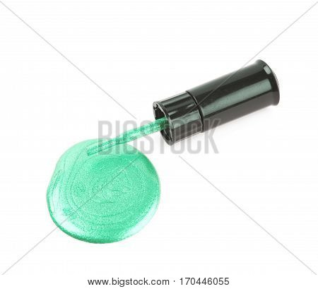 Bottle of nail polish over a puddle of paint, composition isolated over the white background