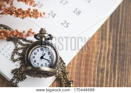 Time for Waiting with Vintage Pocket Watch on the Calendar and Wood Background Image for Deadline Time Concept