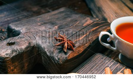 Teacup and anise star on textured old dark brown wood serving boards. Close-up view