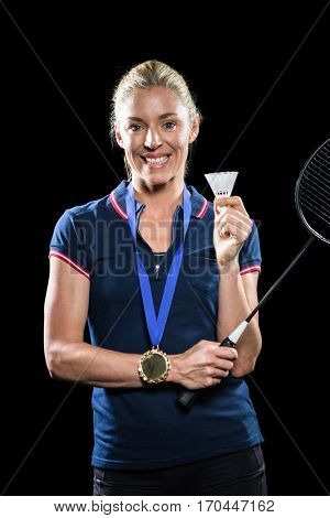 Badminton player posing with gold medal around his neck on black background