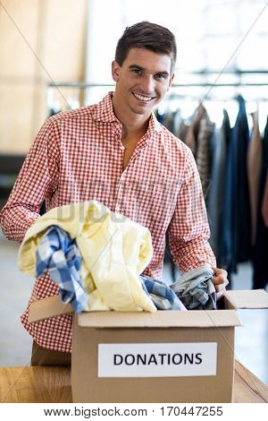 Portrait of young man sorting clothes from donation box while colleague standing in the background