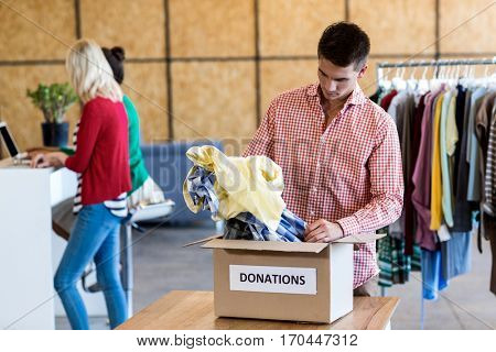 Young man sorting clothes from donation box while colleague standing in the background