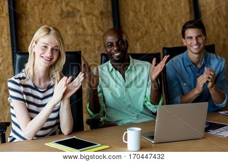Portrait of colleagues applauding at their desk in the office
