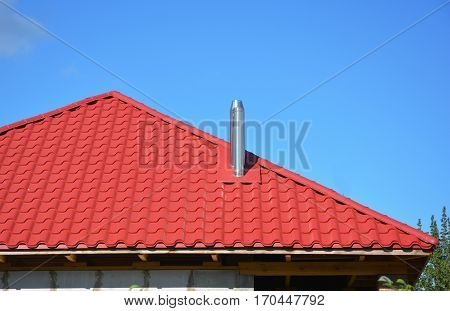 New red metal tiled roof with steel chimney house roofing construction exterior without rain gutter system.