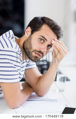 Portrait of worried man with bills on kitchen worktop