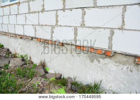 Close up on new building house construction foundation wall waterproofing. Properly insulated basement wall can save you money on heating and provide a dry comfortable living space.
