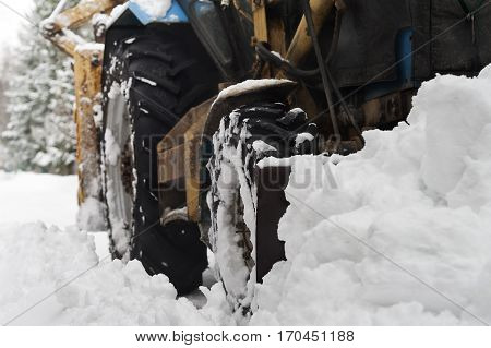 A tractor plowing heavy snow focus in the foreground