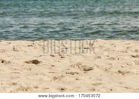 Beauty of nature concept. Symetrical photo of yellow sand and clear blue water