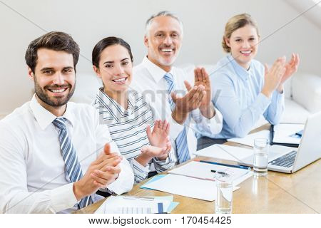 Business colleagues applauding in a meeting at office
