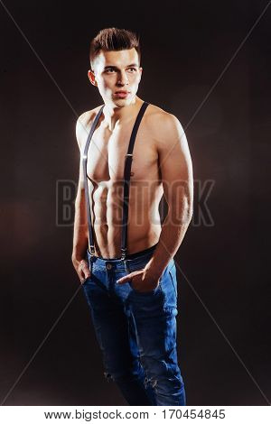 Portrait of a man with nude torso fitness standing in jeans with suspenders, isolated on black.