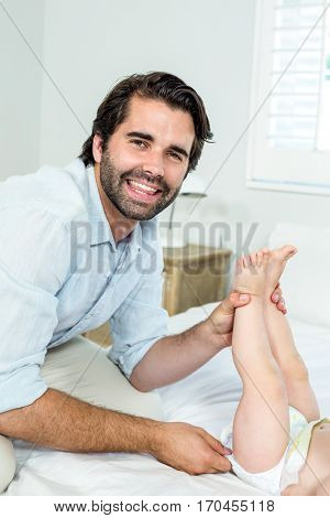 Happy father changing diaper of son on bed at home