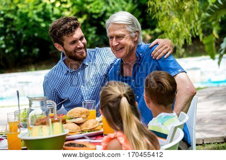 Happy father and son with children at dinning table in lawn