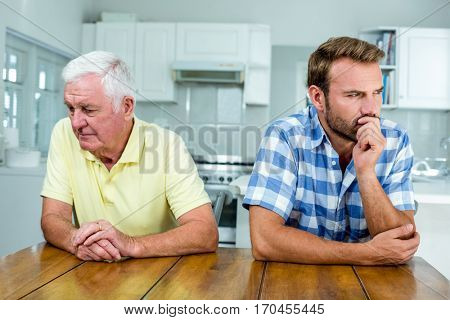 Close-up of tensed father and son sitting at table in kitchen