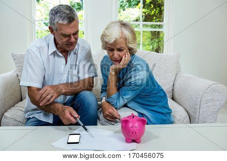 Senior man discussing with wife regarding savings on sofa at home