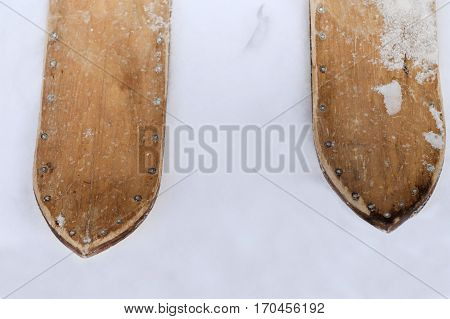 Overhead closeup of the hand made old wooden ski with visible nails standing on the snow