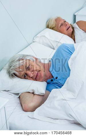Thoughtful senior man relaxing on bed while woman snoring at home