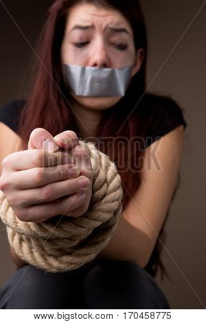 Victim brunette with hands tied