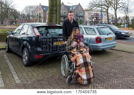 SOEST THE NETHERLANDS - JAN 28: Man pushing a woman in a wheelchair at a parking place in a Dutch village on Januari 28 in Soest the Netherlands