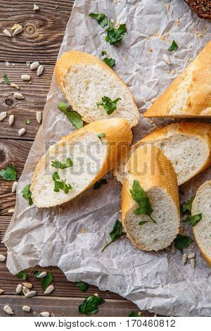 Picture of baguette with herbs on table with seeds