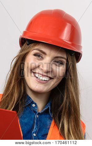 Woman construction worker builder structural engineerin in orange vest red hard helmet. Safety in industrial work. Studio shot