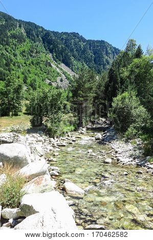 River of Aran valley in the Catalan Pyrenees Spain. The main crest of Pyrenees forms a divide between France and Spain with the microstate of Andorra sandwiched in between