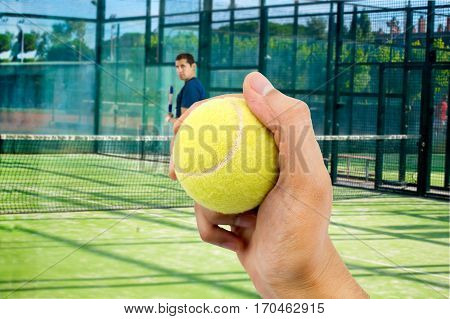 angry man standing in corner of the tennis paddle court because he has lost the match and the rival holds the tennis paddle ball in the foreground