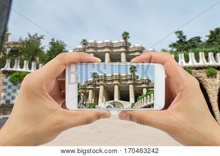 Tourist man taking photo in with smartphone in Park Guell