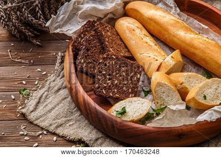 Loaf with brown bread in wooden saucer on table with sunflower seeds and wheat