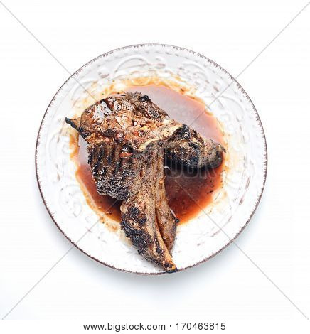 Grilled lamb steak on a plate on a white background