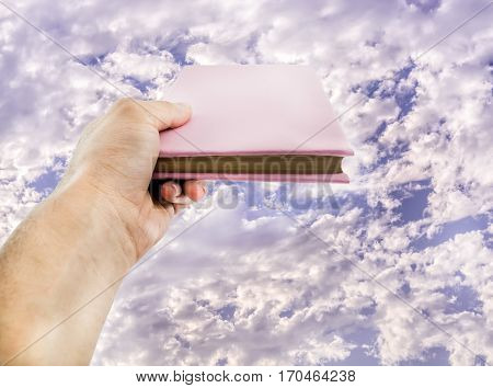 cloudy blue sky over a hand holding a book .conceptual photo of cloud storage, online libraries and shopping of books.holy book with copy space.perspective photography.
