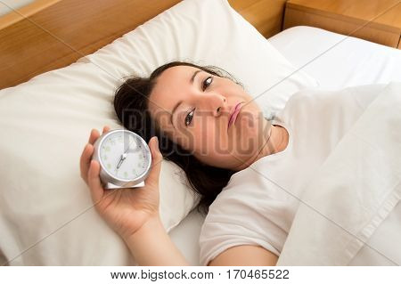 sad woman lying on the bed holding the clock and looking the camera
