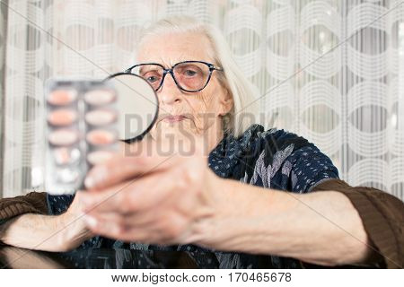 Senior Woman Reading Pill Name With Magnifying Glass