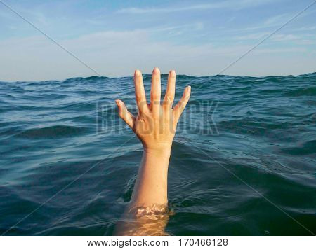 close up of hand drowning in a sea of water