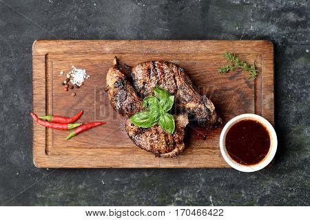 Grilled lamb steak on a cutting board on a dark background