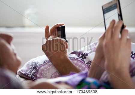 mixed raced couple using smartphone in bed