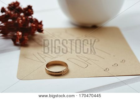 closeup of a golden ring and a brown paper note with the text happy valentines day written in it, on a white table next to a bunch of dry flowers