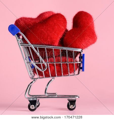 Shopping cart full of hearts for Valentine's Day on pink background