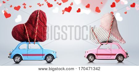 Couple of retro toy cars delivering craft hearts for Valentine's day on gray background with flying hearts