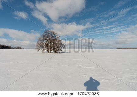 The shadow of the photographer shooting beautiful winter landscape on a Sunny day