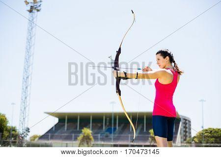 Female athlete practicing archery in stadium