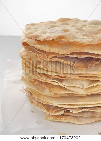 Cooking process. Preparing multi-layered cake. Crusts for homemade mille feuille. Big pile of fresh pancakes. Close up. Side view.